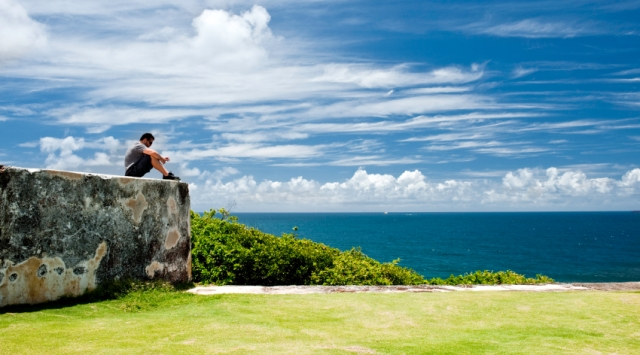 young man relaxing listening to music on top of a stone wall watching the ocean